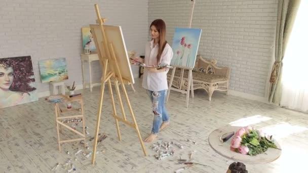 Dívka umělec barvy na plátně: obraz na malířském stojanu