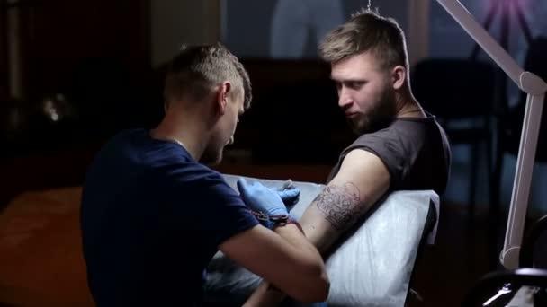 Proces vytváření tetování na mans arm.