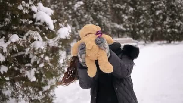 Pregnant girl with Teddy bear in Park in winter.