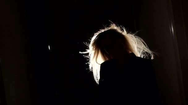 Silhouette eines Mädchens mit flatternden Haaren in dunklem.