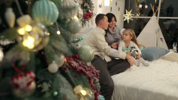 A happy family on the bed with Christmas gifts.