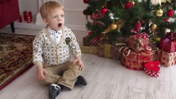 Ein kleiner süßer Junge sitzt auf dem Boden neben einem geschmückten Weihnachtsbaum und gähnt. hohe Auflösung.