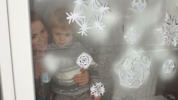 Mutter und Sohn dekorieren Fenster mit Kunstschnee.