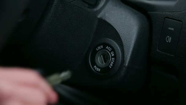 Close-up of the girl turns the ignition key in car
