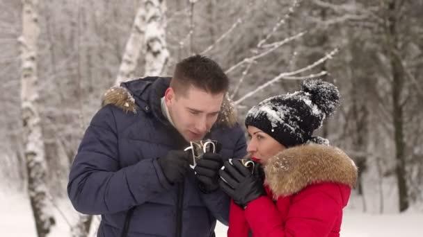 Verliebtes Paar trinkt heißen Tee im Winterpark