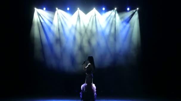 Gyönyörű lány énekel egy dalt a megvilágított színpadon.