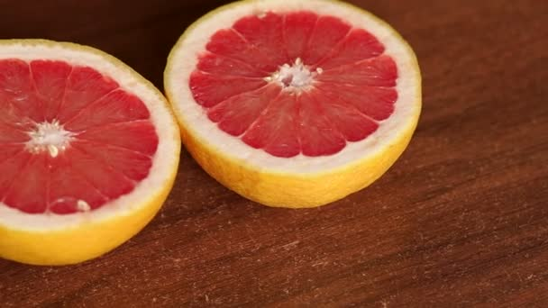 Cut grapefruit on a brown wooden surface. Close-up