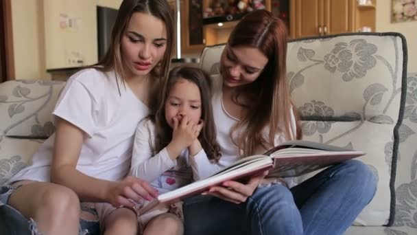 Three sister look photo album sitting on couch.