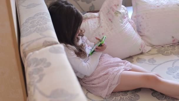 Child lying on couch with a phone in her hand.