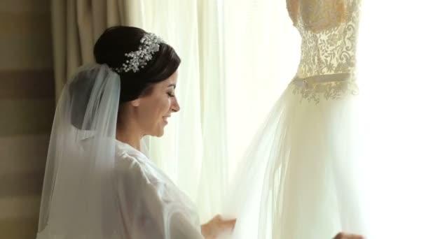 Menyasszony csodálja, és megérinti a ruhája, ablak közelében.