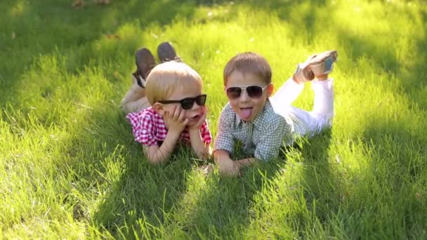 Portrait of young children in sunglasses on grass.