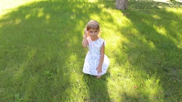Malá sladká holka sedí na trávě v parku.