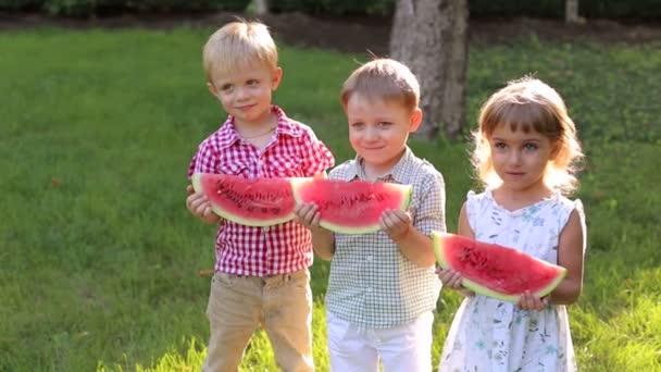 Tři děti jíst meloun na trávě v parku