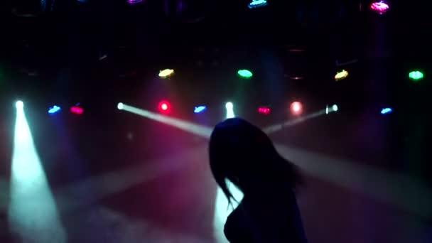 Siluetta di una ragazza snella che balla in discoteca.