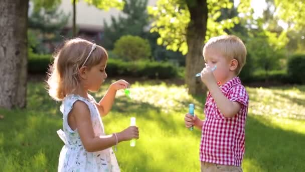 Little kids are playing with soap bubbles in Park.