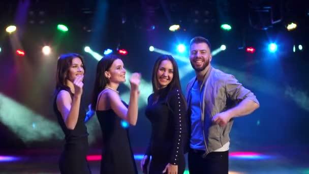Group of friends dance in a nightclub in the dark.