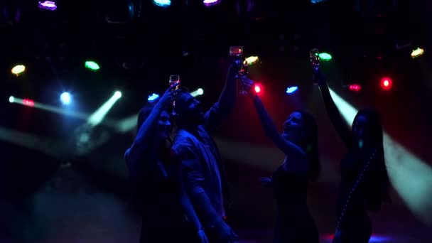 Group of teenagers dancing in a disco, silhouette.