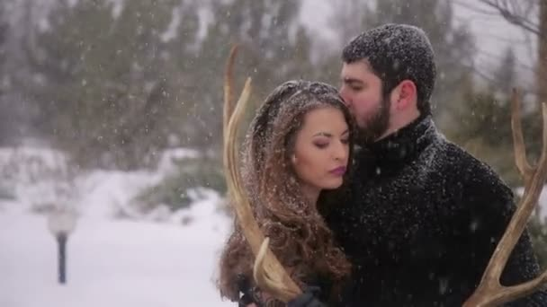Couple in black clothes under heavy snow. Wedding.