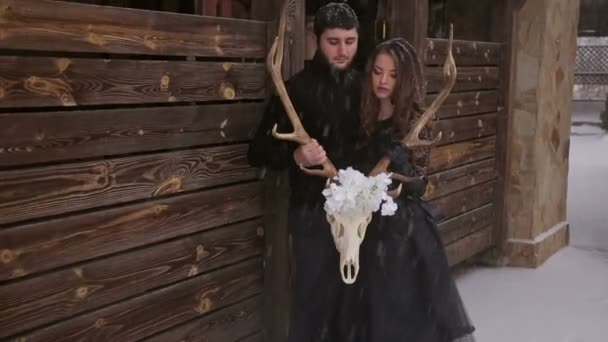 Couple in black clothes holding a skull under snow