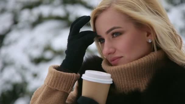 Dívka s kávou v parku zasněženou zimní.