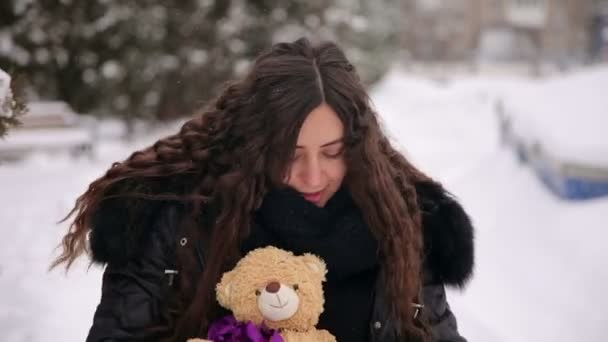 Portrait of a pregnant with a Teddy bear in winter