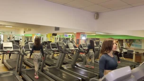 Jungen Sportler, die Frau im Fitness-Studio arbeitet. Cardio-Training. Läuft auf Laufband.
