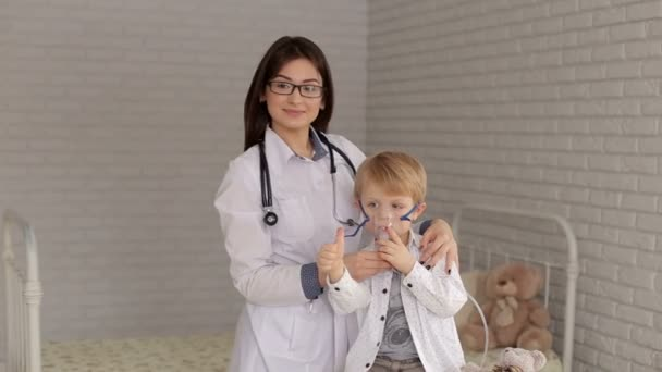 Kinderarzt hält einem kleinen Jungen, der durch einen Dampfvernebler atmet, eine Maske mit Dampfinhalator vor. der Arzt und das Kind mit Inhalationsmaske, Daumen hoch, Portrait.