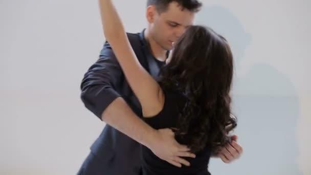 Young couple dancing the salsa or bachata at the dance hall.