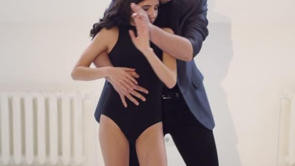 flexible Tänzer tanzen Standardtänze in einem hellen Raum mit kleinen Fenstern.
