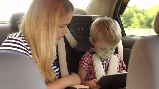A caring mother sits next to the child in the car, they play the tablet.