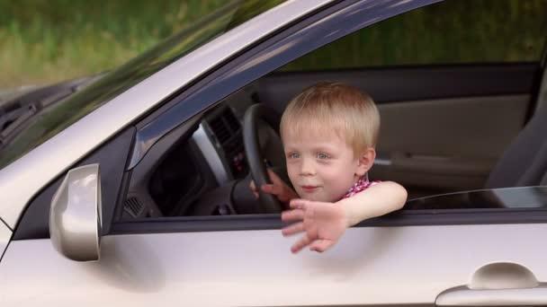 Portrét dítěte, kdo se dívá z okna auta v létě.