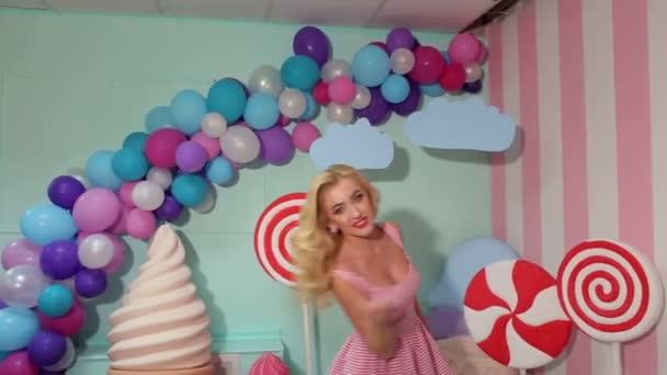 Portrét veselá dívka v růžové pruhované šaty na pozadí velké sladkosti
