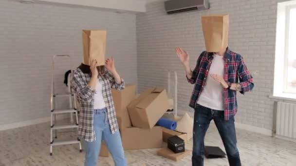 Portrét veselá mladých lidí, kteří kladou na jejich hlavách papírové sáčky, kolaudační