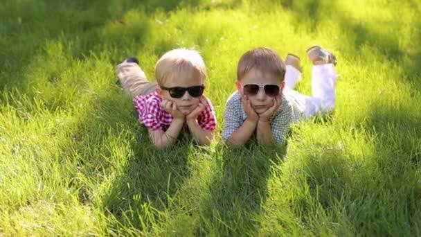 Két vidám boldog kis fiú feküdni a fűben, napszemüveg, nyáron. Portré