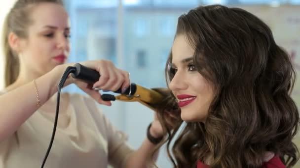 Fodrász csinál a frizura a modell hajcsavarók segítségével a fodrász.