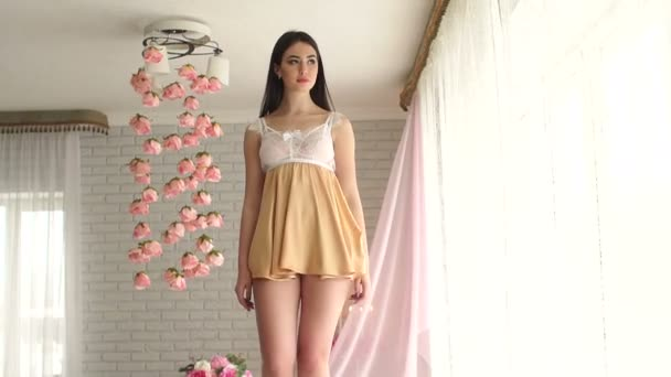Mladá dívka v sexy prádlo a krátké negližé pózuje pro kamery.