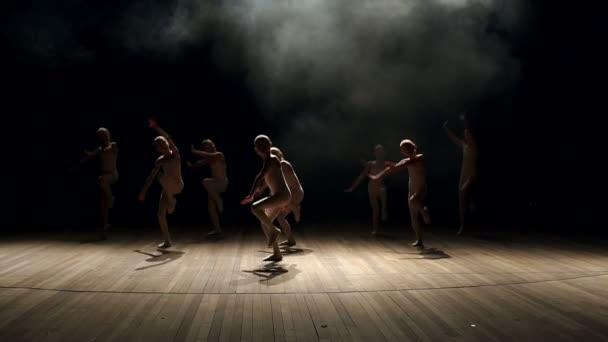 Silueta malých dětí tanec na jevišti na černém pozadí. Balet