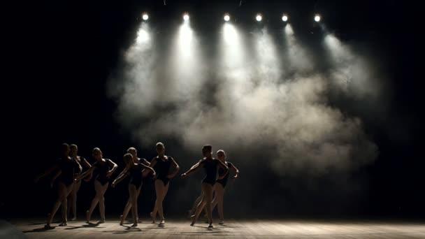 Rugalmas lányok táncolni a színpadon, a fekete háttér balett-táncosok csoportja.
