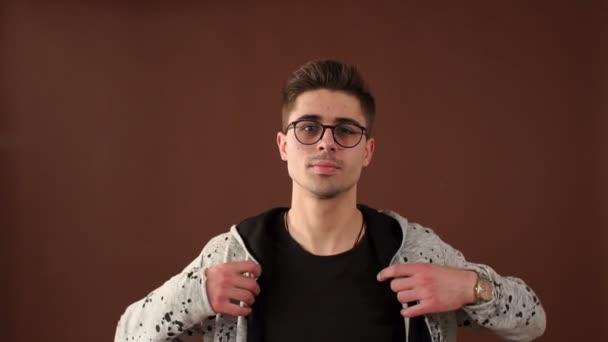 Közelkép portré egy elegáns fiatal srác egy sport pulóver, barna háttér