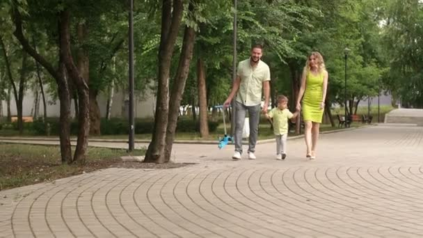 Mom with dad and little son walk in the Park in summer with childrens scooter.