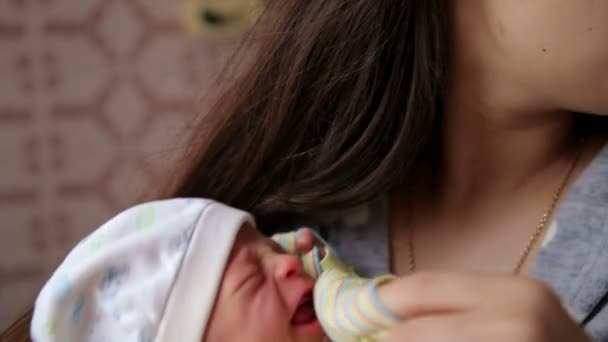 Sweet crying newborn baby at mom on hands. Newborn crying baby. Children cry.