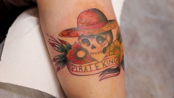 Close-up of a tattoo with a skull on the hand of a man. Tattoo parlor.