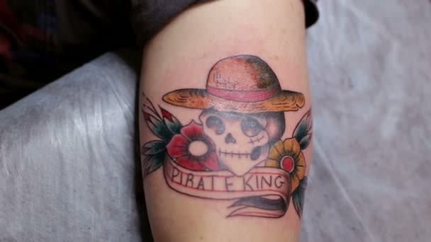 Közeli kép: a tetoválás egy koponya, egy férfi keze. Tetováló szalon.