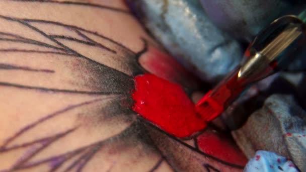 Csinál egy ember, ő tölti ki a tetoválás vörös tintával körvonalú tattoo tetováló művész