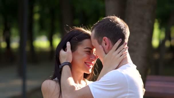 Portréja egy pár a parkban, a fák ellen napnyugtakor, ölelés, és csók.