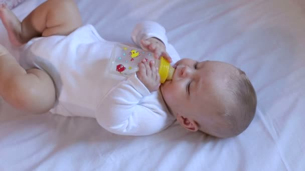 A newborn baby is lying on the bed and drinking water or milk from the bottle.