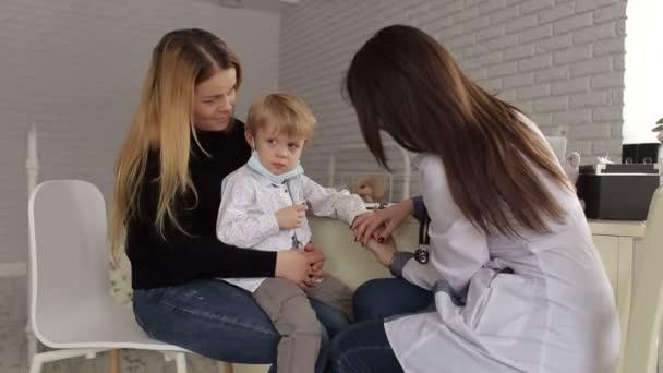 Ärztin hält Hand über kleinen Jungen mit Pflege im Krankenhaus.
