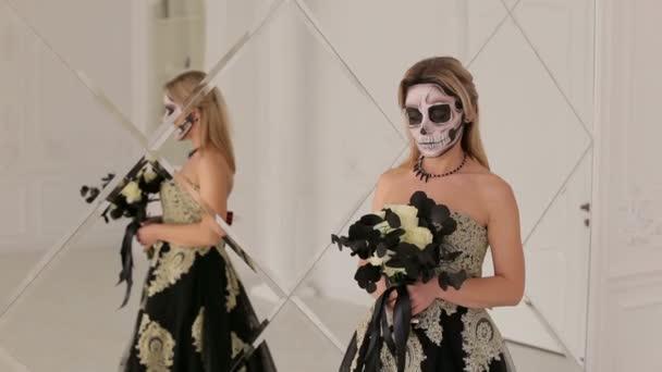 Ein Mädchen in einem Kleid und Make-up in Form eines Skeletts auf Halloween.