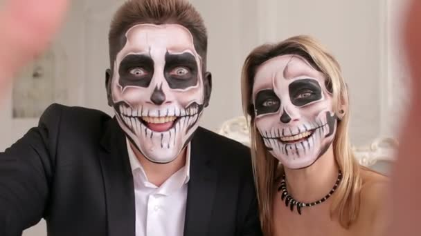 Creepy couple with scary Halloween makeup make selfies in a studio.