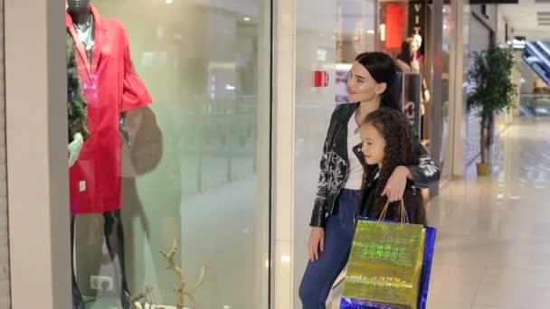 Módní mladá dívka s mladší sestrou v obchoďáku a zastavili se u okna a díval se na oblečení figurín.